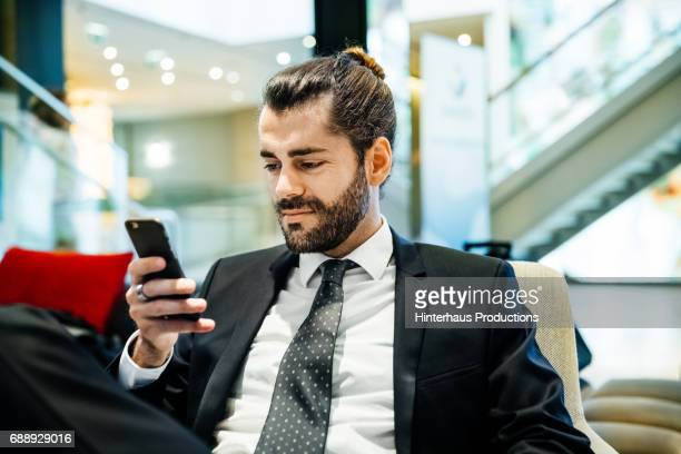 Stylish Young Businessman Smiling Whilst Looking At His Phone