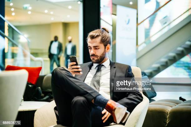 Stylish Young Businessman Using His Phone In A Hotel Foyer