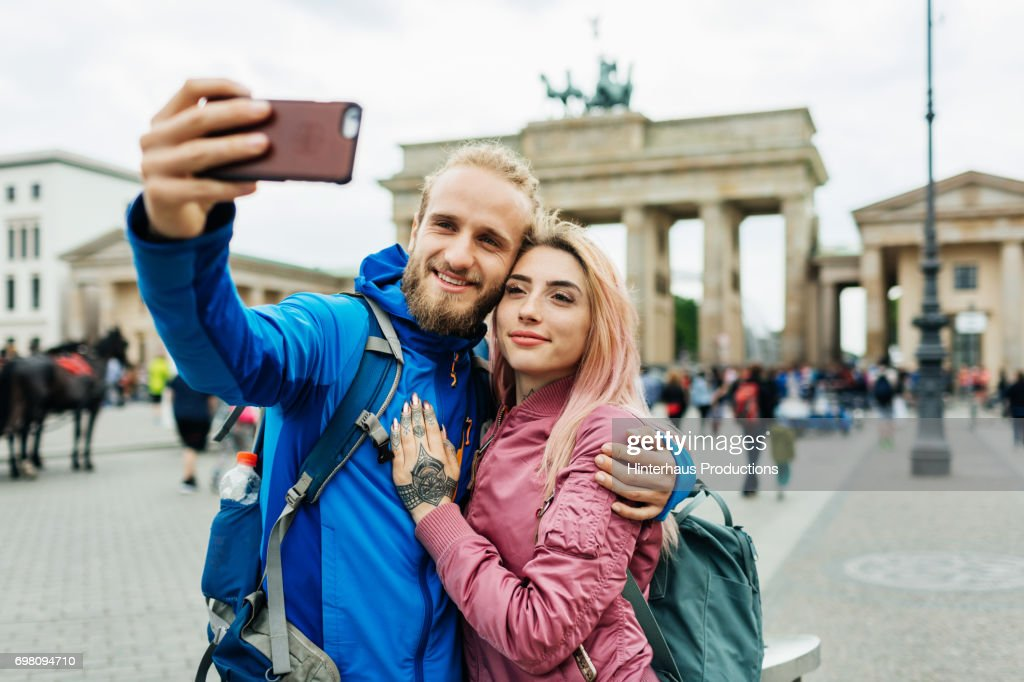 Stylish Young Couple Take A Selfie In Front Of Local Architecture : Stock Photo
