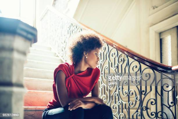 stylish young cuban woman sitting on stairs indoors - red dress stock photos and pictures