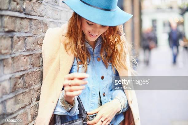 stylish young female shopper fastening handbag, london, uk - evening bag stock pictures, royalty-free photos & images