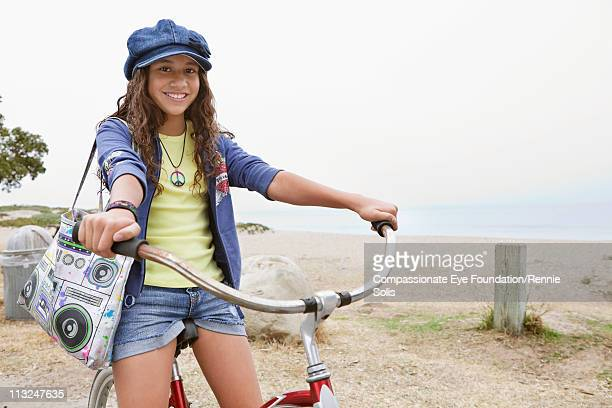 stylish young girl sitting on bicycle - hot pants stock-fotos und bilder