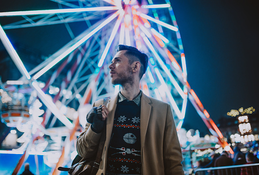 Stylish young man at a carnival/funfair standing in front of a big wheel - gettyimageskorea
