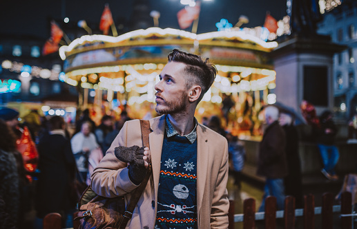 Stylish young man at a carnival/funfair standing in front of a carousel - gettyimageskorea