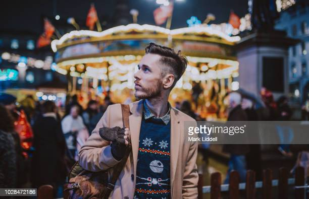 Stylish young man at a carnival/funfair standing in front of a carousel