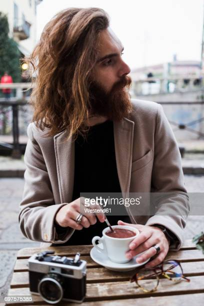 Stylish young man at a street cafe looking around