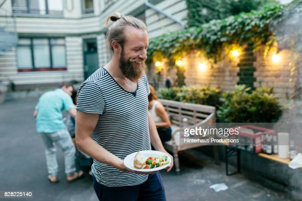 Stylish Young Man At Barbecue With Friends Smiling As He Loads Plate With Food