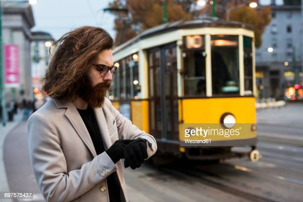 stylish young man checking the time at tram stop - milan street style stock photos and pictures