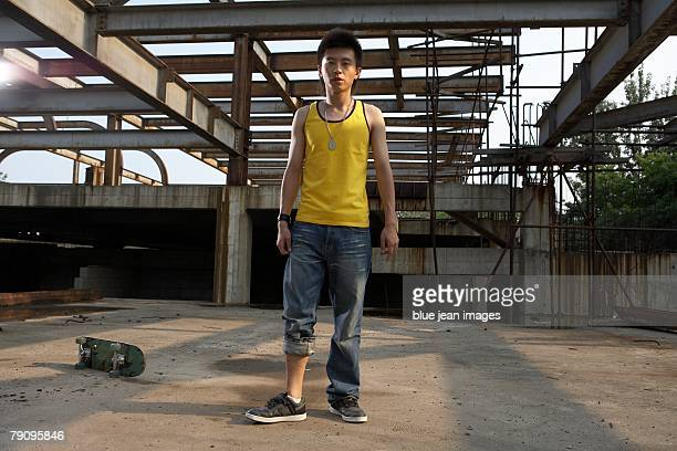 a stylish young man covers his ears and yells while relaxing with his bike in an abandoned industrial area. - baggy jeans stock photos and pictures