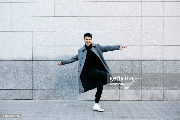 stylish young man dancing on the street - casacca foto e immagini stock