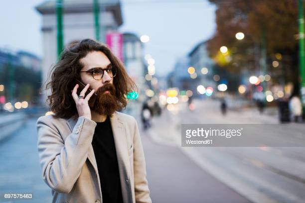 Stylish young man in the city on cell phone