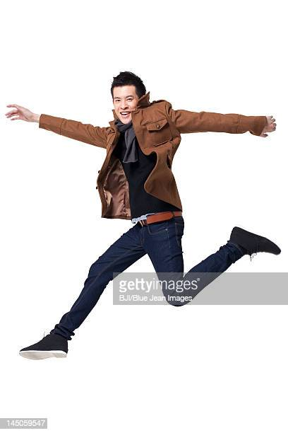 Stylish young man jumping in mid-air