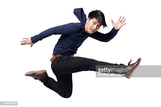 stylish young man jumping in mid-air - striding stock pictures, royalty-free photos & images