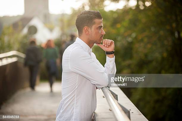 Stylish young man leaning on railing of a footbridge