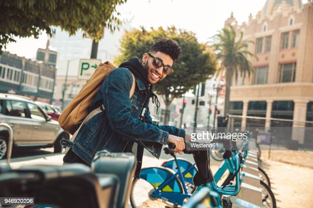 stylish young man on the street with rental bike - bicycle parking station stock photos and pictures