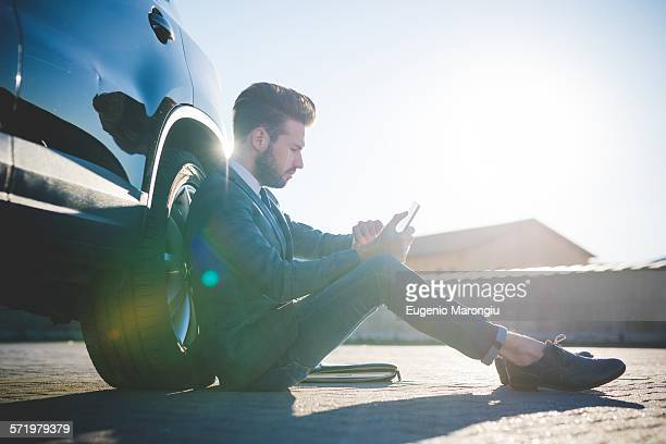Stylish young man sitting leaning against car using digital tablet