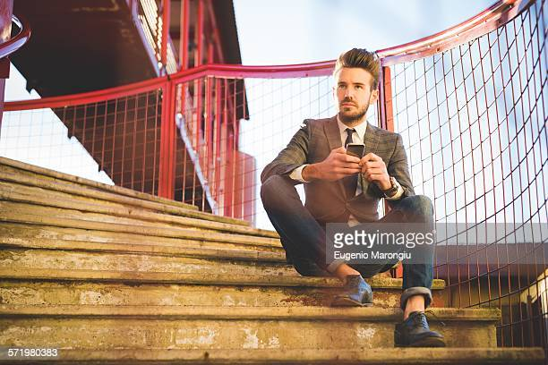 Stylish young man sitting on footbridge stairs with smartphone