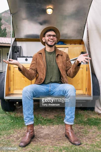 Stylish young man sitting on travel trailer