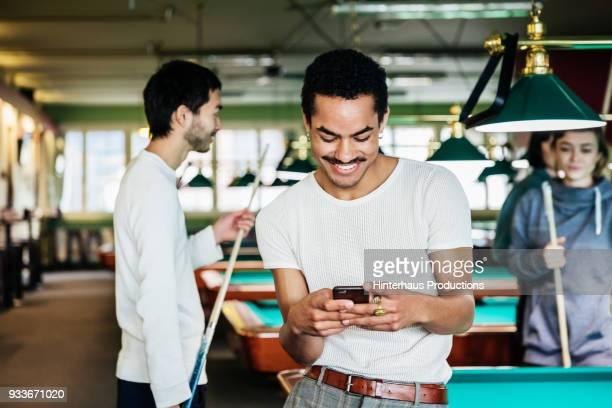 stylish young man smiling while using smartphone at pool hall - poolbillard billard stock-fotos und bilder