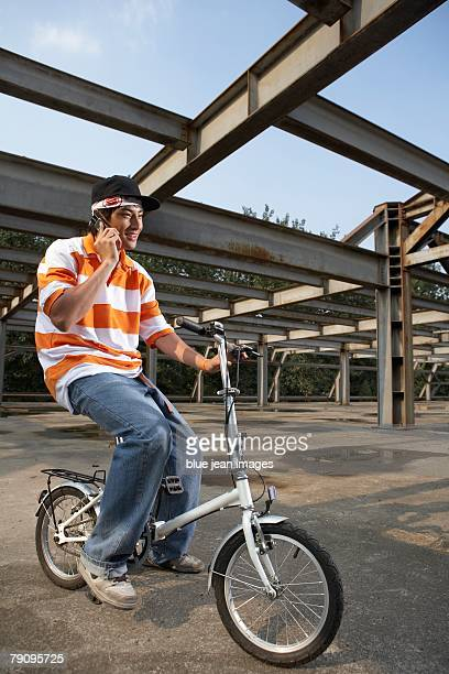 a stylish young man uses his cell phone while riding his bike in an abandoned industrial area. - baggy jeans stock photos and pictures