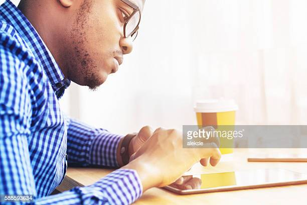 Stylish young man using tablet pc at home