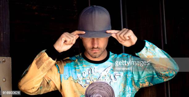 stylish young man wearing basecap and printed shirt - bones - fotografias e filmes do acervo