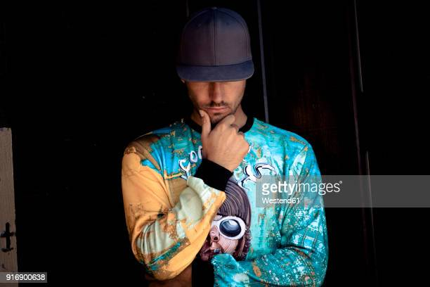 stylish young man wearing basecap and printed shirt - cap stock pictures, royalty-free photos & images