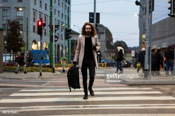 Stylish young man with bag crossing street on zebra crossing