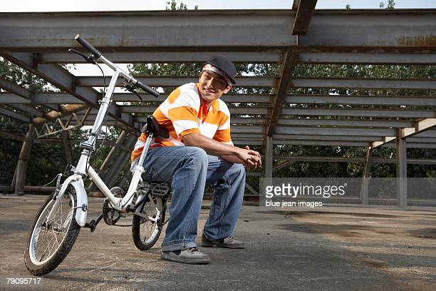 A stylish young man with his bike in an abandoned industrial area.