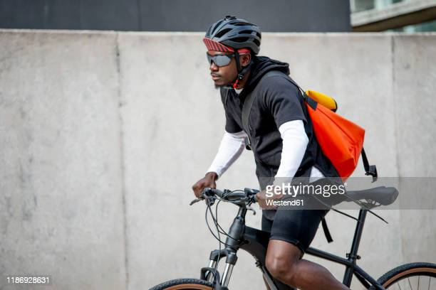 stylish young man with messenger bag riding bicycle in the city - bicycle messenger stock pictures, royalty-free photos & images