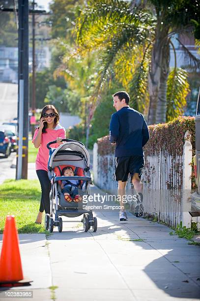 stylish young Mom with baby, runner passing