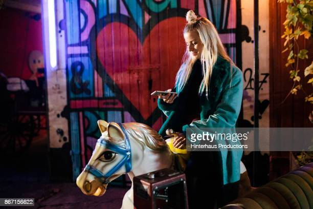stylish young partygoer riding on a mechanical horse at open air nightclub - leben in der stadt stock-fotos und bilder
