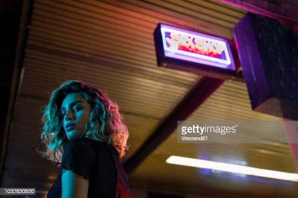stylish young woman at night, standing in front of sex shop - red light district stock-fotos und bilder