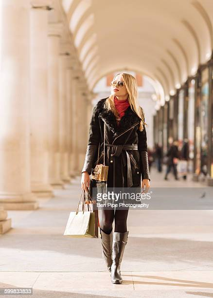Stylish young woman carrying shopping bags, Covent Garden, London, UK