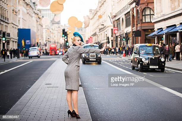 A stylish young woman dressed in 1930s style clothing hailing a taxi on Regent Street in London