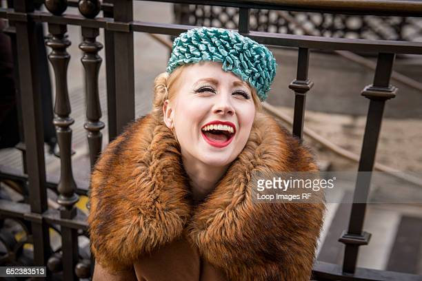 A stylish young woman dressed in 1930s style clothing sitting laughing by railings at the entrance to Piccadilly Circus tube station