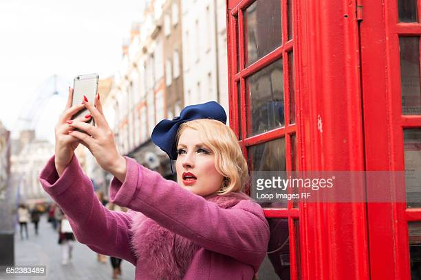A stylish young woman dressed in 1930s style clothing taking a selfie outside a traditional telephone kiosk on a London street