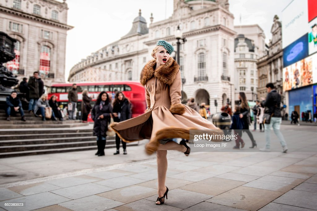 A stylish young woman dressed in 1930s style clothing twirling around by the statue of Eros at Piccadilly Circus : Stock-Foto