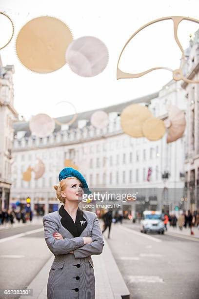 A stylish young woman dressed in 1930s style clothing waiting for a taxi on Regent Street in London