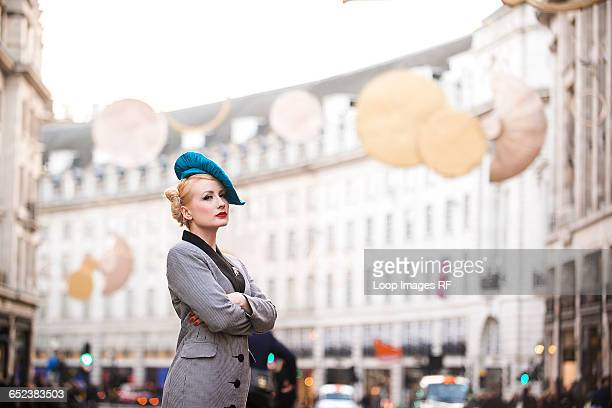 a stylish young woman dressed in 1930s style clothing waiting for a taxi on regent street in london - mulher fatal imagens e fotografias de stock