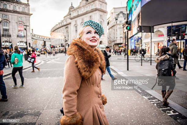 a stylish young woman dressed in 1930s style clothing walking about at piccadilly circus - 1930~1939年 ストックフォトと画像