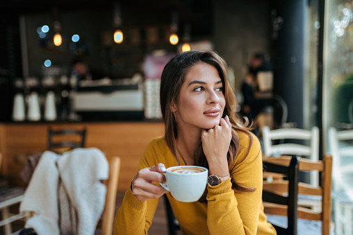Stylish young woman drinking coffee at the cafe, looking away. 1069585056