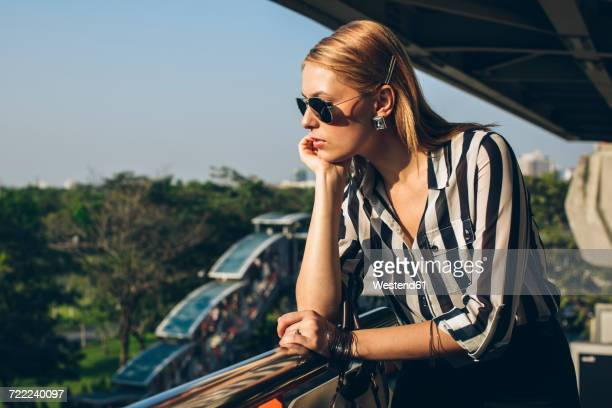 Stylish young woman enjoying sunlight on terrace