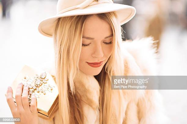 Stylish young woman holding gold jewelry box, Covent Garden, London, UK
