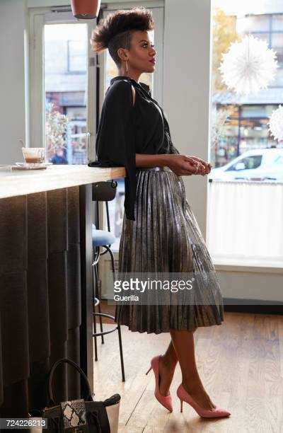 Stylish young woman leaning on counter in a cafe, side view