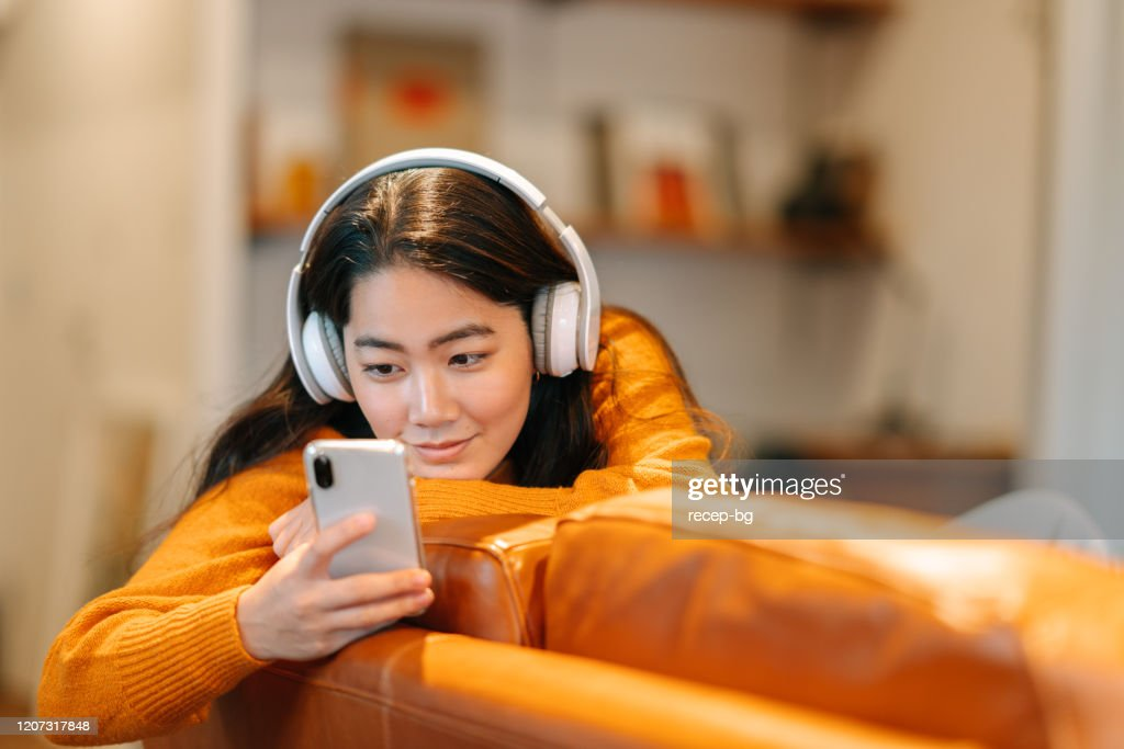 Stylish young woman listening to music at home : Stock Photo