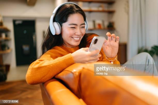 stylish young woman listening to music at home - só uma mulher jovem imagens e fotografias de stock