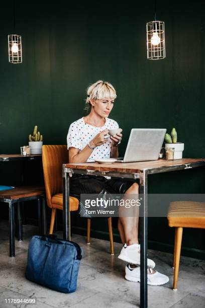 stylish young woman looking at laptop in coffee shop - europa occidentale foto e immagini stock