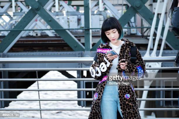 stylish young woman looking at smartphone on millennium footbridge, london, uk - アニマルプリント ストックフォトと画像