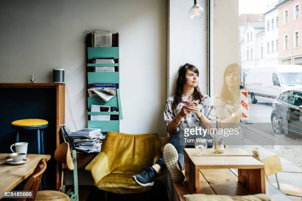 stylish young woman looking out window in cafe - 足を組む ストックフォトと画像